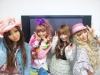 A very cute group of girls with various styles pose with smiles and peace signs.