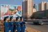 Four traffic ladies on a sunny day in Pyongyang. Official government posed picture with requisite propaganda poster in background.