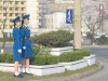 A couple Pyongyang Traffic Girls, on a grassy median - one possibly waiting to relieve an on duty traffic girl.